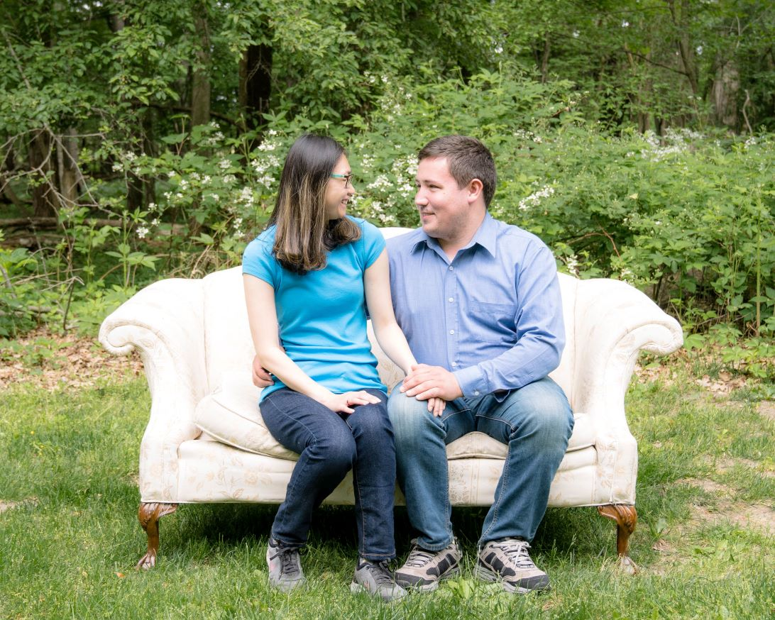 hopeful adoptive parents sitting on a sofa looking excited to start the adoption process