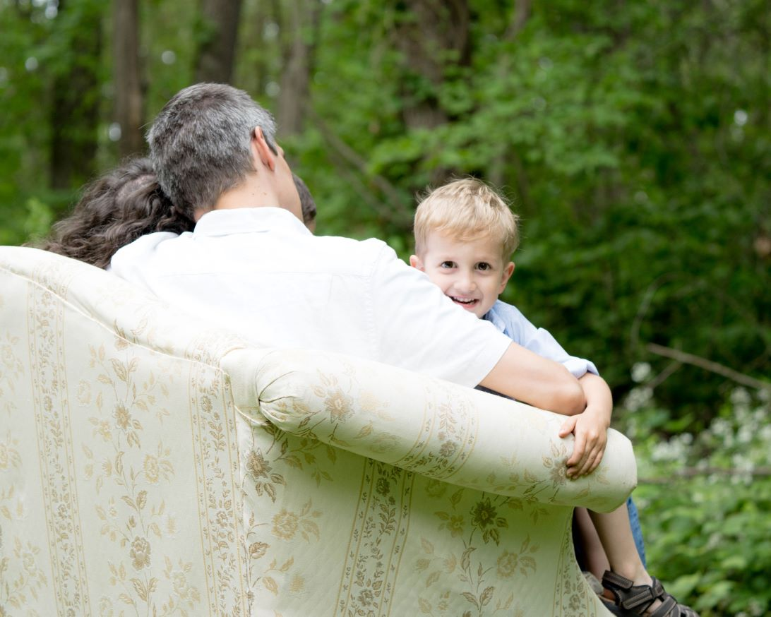 smiling blonde adopted boy peering over the sofa while sitting on his dad's lap