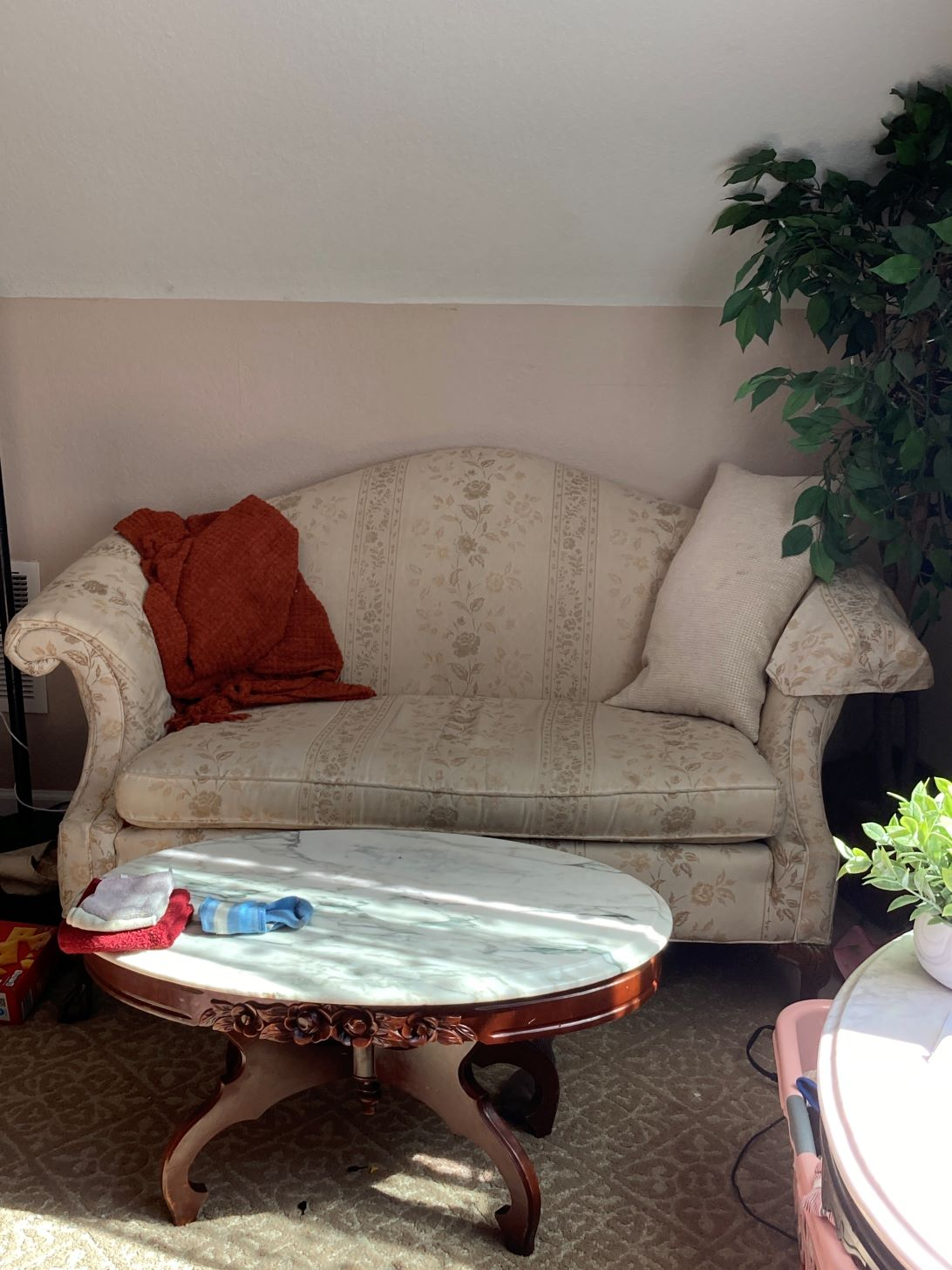 white floral sofa in a living room with pillows