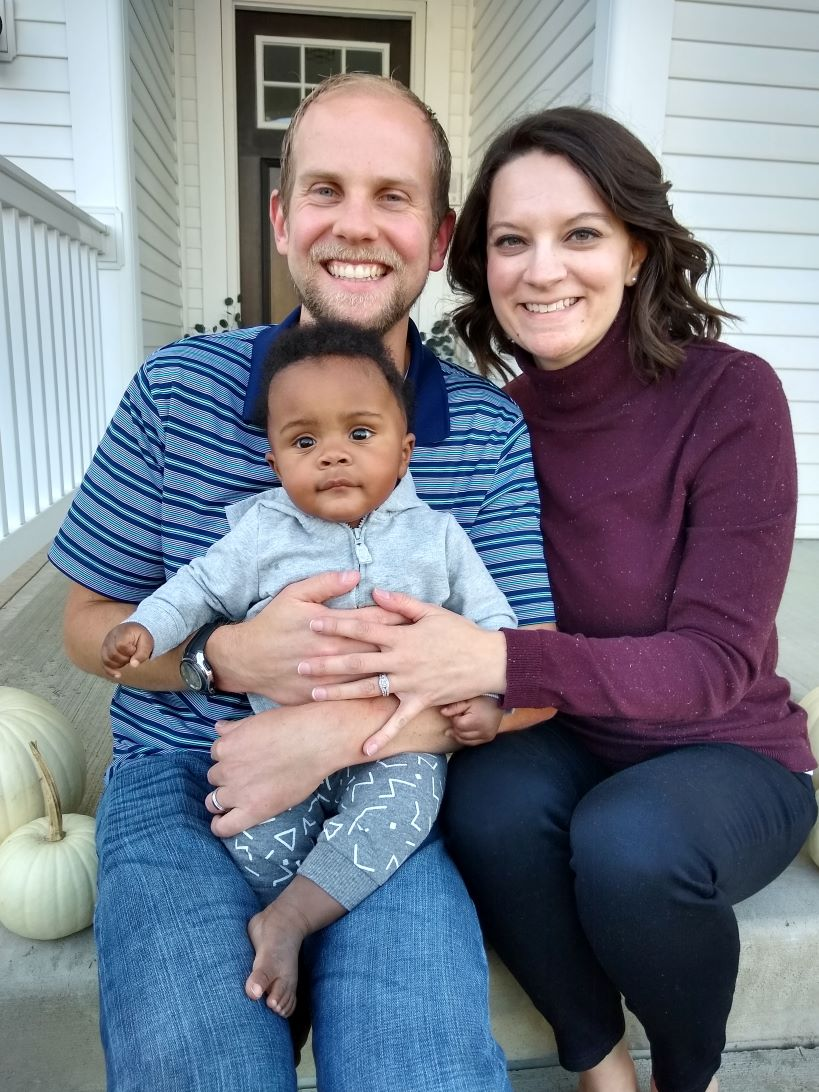 Seth and Megan sitting on their front porch with their infant son, ready to adopt in Ohio through Spirit of Faith Adoptions.